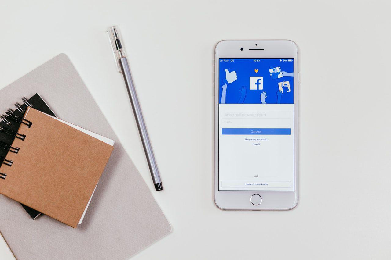 Smartphone mit geöffneter Facebook-Seite auf einem Tisch